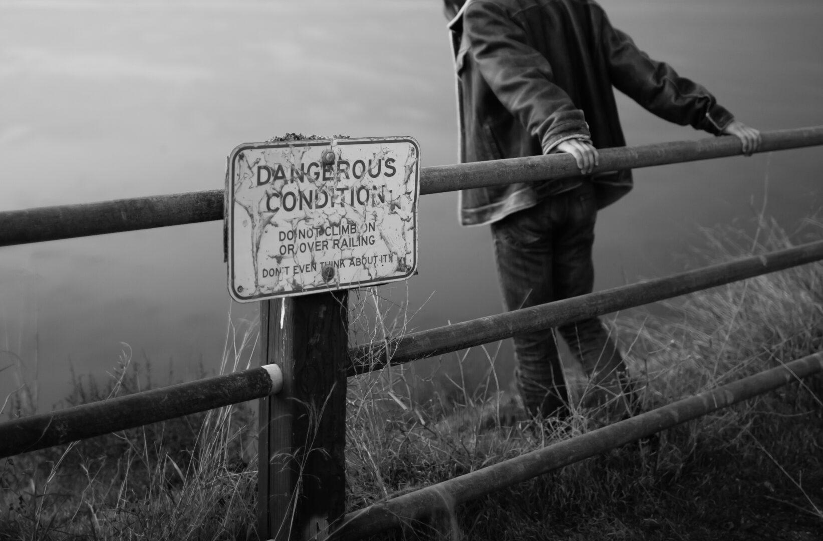 A man at the edge of a bridge, holding onto railings